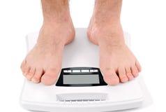 Mann, der auf Gewichtsskala steht lizenzfreie stockfotos