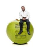 Mann, der auf grünem Apple mit Nahrung-Kennsatz sitzt Stockbild
