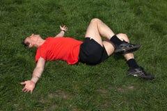 Mann, der auf Gras trainiert und ausdehnt lizenzfreie stockfotos