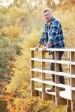 Mann, der auf hölzernem Balkon im Waldland steht Stockfotografie