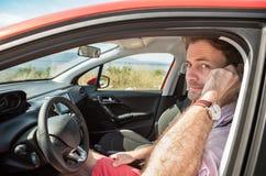 Mann, der auf Handy u. x28 spricht; smartphone& x29; in einem Auto Stockfoto