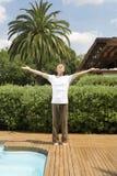 Mann, der auf Klappstuhl im Garten stützt Lizenzfreies Stockbild