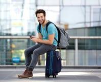 Mann, der auf Koffer sitzt und Textnachricht sendet Stockfoto