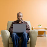 Mann, der auf Laptop im Wohnzimmer schreibt Stockfotografie