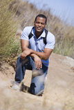 Mann, der auf Pfad sich duckt, um das Lächeln auf den Strand zu setzen Stockfoto