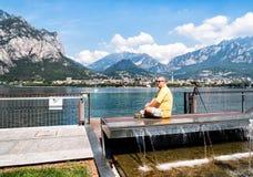 Mann, der auf Pier von Como See sitzt stockfotos