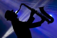 Mann, der auf Saxophon vor dem hintergrund des schönen lig spielt Lizenzfreie Stockbilder