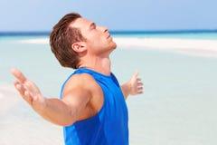 Mann, der auf schönem Strand meditiert Lizenzfreies Stockbild