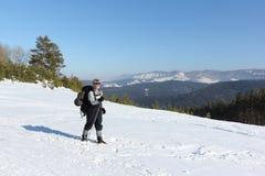 Mann, der auf Schnee unter Bergen wandert Lizenzfreie Stockbilder