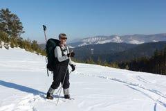 Mann, der auf Schnee unter Bergen wandert Lizenzfreies Stockfoto