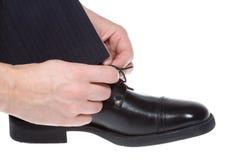 Mann, der auf schwarzen Schuh sich setzt stockfotos