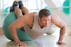 Mann, der auf Schweizer Kugel an der Gymnastik balanciert Lizenzfreies Stockfoto