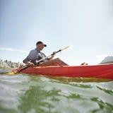 Mann, der auf See im Sommer Kayak fährt Lizenzfreies Stockfoto