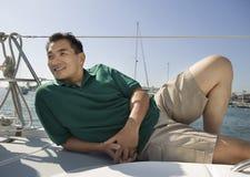 Mann, der auf Segelboot sich entspannt Lizenzfreie Stockbilder