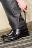 Mann, der auf seine Schuhe sich setzt. stockfotografie