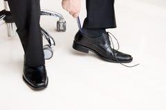 Mann, der auf seine Schuhe sich setzt Lizenzfreies Stockbild