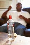 Mann, der auf Sofa With Bottle Of Vodka und Zigaretten sitzt Lizenzfreie Stockbilder
