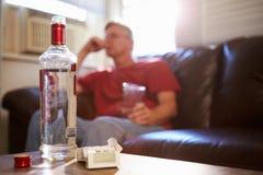 Mann, der auf Sofa With Bottle Of Vodka und Zigaretten sitzt Lizenzfreies Stockbild