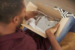 Mann, der auf Sofa At Home Opening Online-Kleidungs-Kauf sitzt Stockfoto