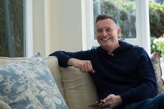 Mann, der auf Sofa In Living Room sitzt lizenzfreie stockfotografie