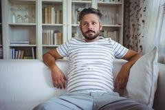 Mann, der auf Sofa In Living Room sitzt lizenzfreie stockfotos