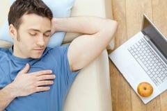 Mann, der auf Sofa schläft Lizenzfreies Stockbild