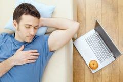 Mann, der auf Sofa schläft Lizenzfreie Stockfotografie
