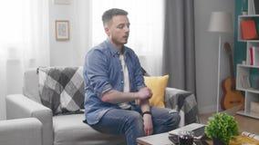 Mann, der auf Sofa sitzen und Ende, das auf Laptop-Computer arbeitet stock video footage