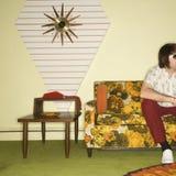 Mann, der auf Sofa sitzt. Stockfotos