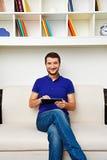 Mann, der auf Sofa sitzt Stockbild