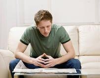 Mann, der auf Sofalesezeitung sitzt Lizenzfreies Stockbild