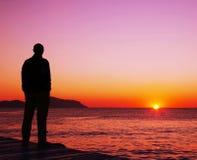 Mann, der auf Sonnenuntergang schaut Lizenzfreies Stockfoto