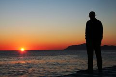 Mann, der auf Sonnenuntergang schaut Stockbild