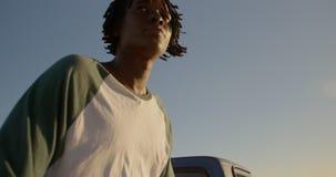 Mann, der auf Stamm des Kleintransporters am Strand 4k sitzt stock footage