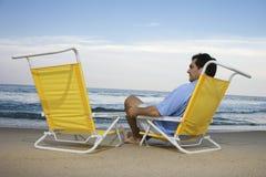 Mann, der auf Strand alleine sitzt Stockbilder