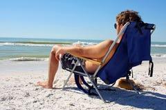 Mann, der auf Strand durch Ozean ein Sonnenbad nimmt Stockbilder
