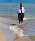 Mann, der auf Strand mit Wellen geht Lizenzfreie Stockbilder