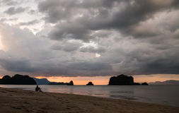 Mann, der auf Strand nach Sonnenuntergang sitzt Lizenzfreies Stockfoto