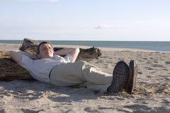 Mann, der auf Strand schläft Stockfotos