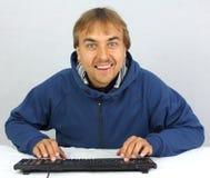 Mann, der auf Tastatur und dem Lächeln schreibt Stockfoto