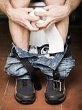 Mann, der auf Toilettenschüssel sitzt Stockfotos