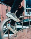 Mann, der auf tragenden Jeans und Mokassinen eines Zauns sitzt stockfotografie