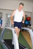 Mann, der auf Tretmühle an der Gymnastik läuft Lizenzfreies Stockbild