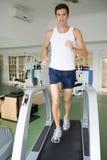 Mann, der auf Tretmühle an der Gymnastik läuft Lizenzfreie Stockfotos