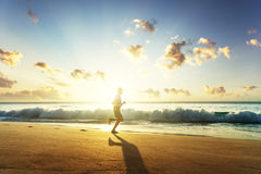 Mann, der auf tropischem Strand bei Sonnenuntergang läuft Stockbild