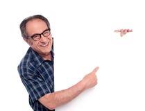 Mann, der auf weißes unbelegtes Plakat zeigt Lizenzfreies Stockfoto