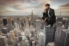 Mann, der auf Wolkenkratzer sitzt Stockfotografie