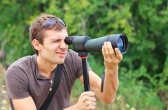 Mann, der in Aufdeckungsbereich aufpasst Positiver Mann, der durch ein Teleskop schaut Stockbild