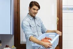 Mann, der Aufgabe- und Waschenkleidung tut Stockfoto