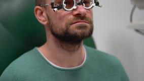 Mann an der Aufnahme eines Augenarzt Sehtests und der Auswahl der Brillengläser stock footage